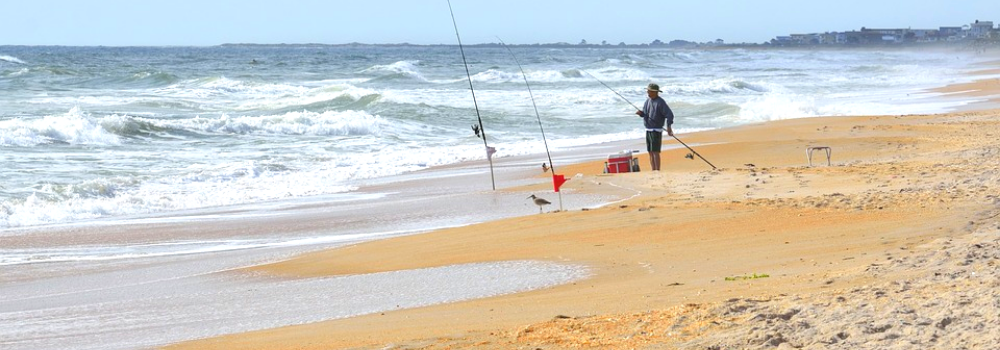Image contains a fisherman on the beach.